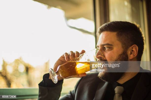 Businessman drinking beer at the bar