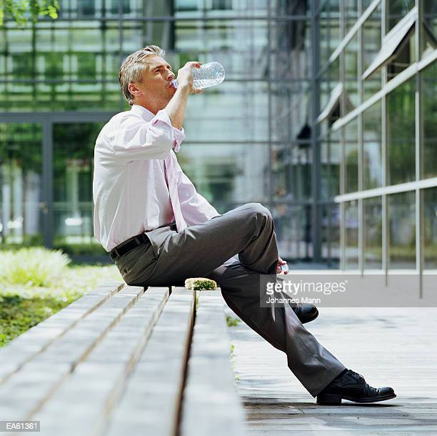 Businessman drinking bottle of water outdoors
