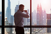 Young Businessman Drinking A Coffee While Looking At The City Skyline