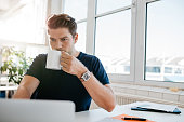 Young businessman drinking coffee and working on laptop at office. Male executive working at his desk and drinking coffee.