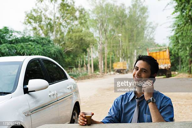 Businessman drinking tea and talking on a mobile phone