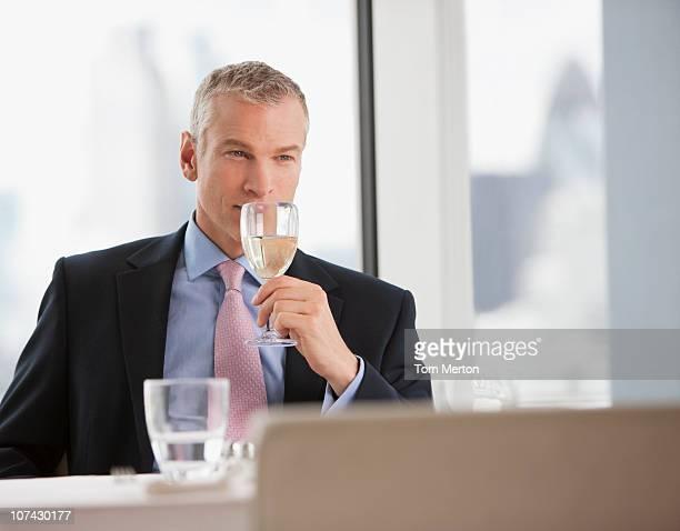 Empresario bebiendo vino blanco en el restaurante