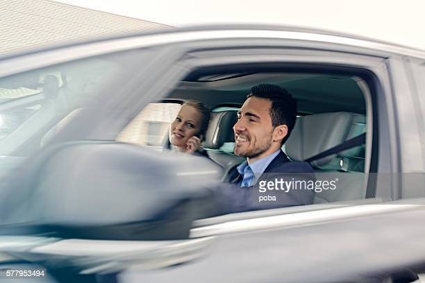 businessman driving  a car with his colleague
