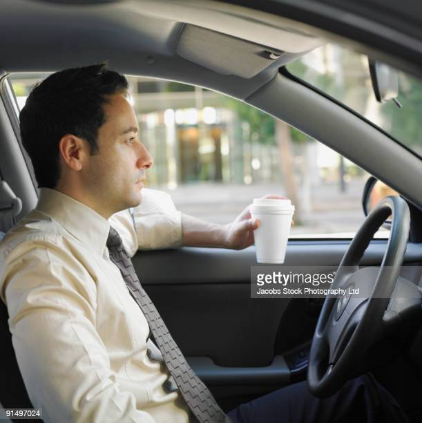 Businessman driving and drinking coffee
