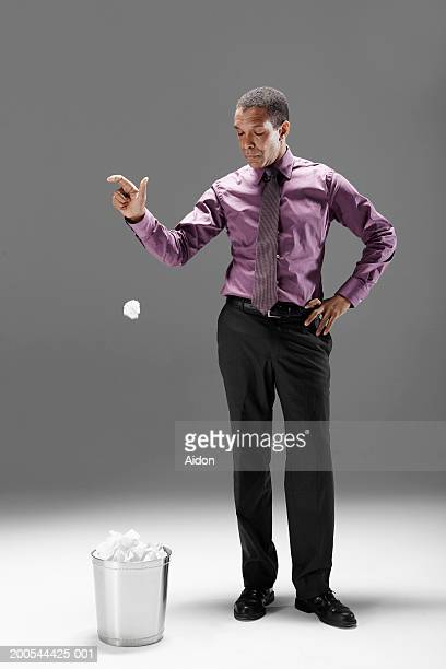 Businessman dropping crumpled paper into waste basket, studio shot