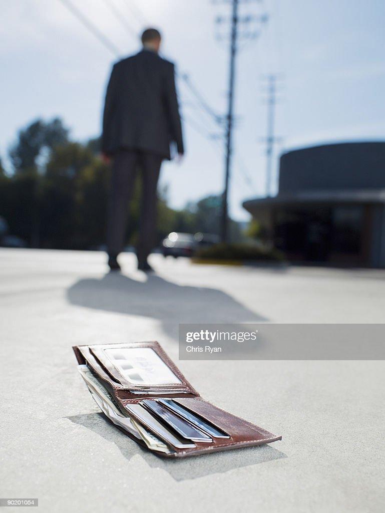 Businessman dropping wallet on sidewalk : Stock Photo