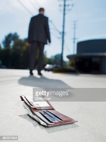Businessman dropping wallet on sidewalk : Stock Photo