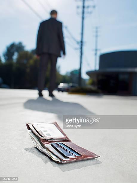 Businessman dropping wallet on sidewalk