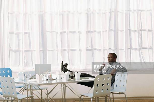 Businessman eating apple at empty conference table