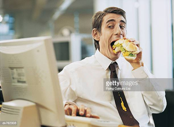 Businessman Eating at His Desk With a Mustard Stain on His Tie