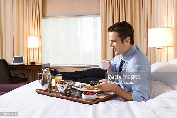 Businessman eating breakfast on bed in hotel room