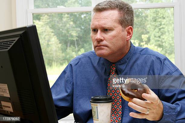 Businessman eating doughnut and coffee at computer