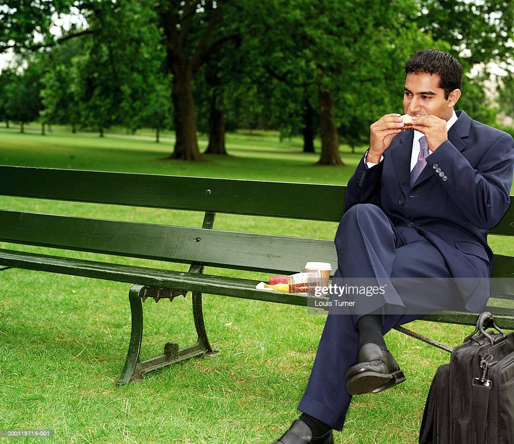 Businessman eating lunch on park bench : Stock Photo