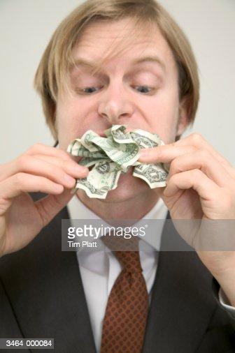 Businessman Eating Money : Stock Photo