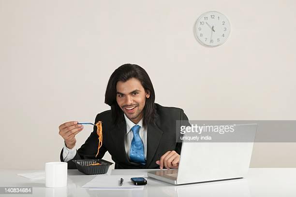 Businessman eating noodles at the desk