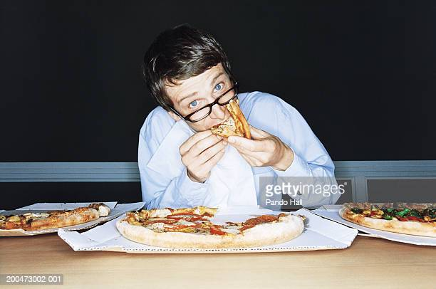 Businessman eating pizza from boxes on table, portrait