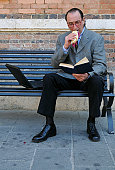 Businessman Eating Snack Reading Book on a Bench