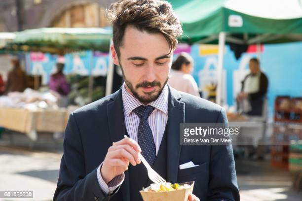 Businessman eating street food, walking through urban food market.