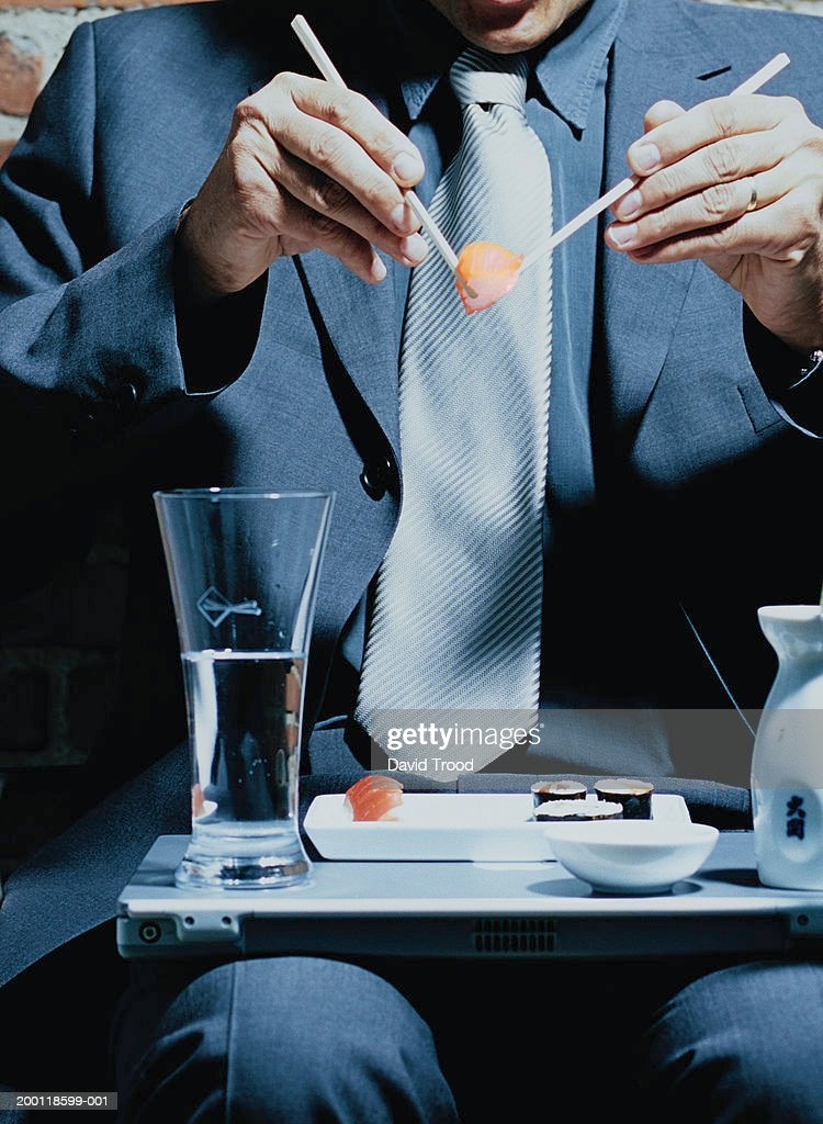 Businessman eating sushi from plate balanced on laptop, mid section