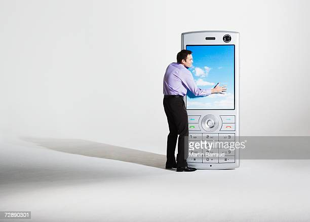 Businessman embracing giant model mobile phone