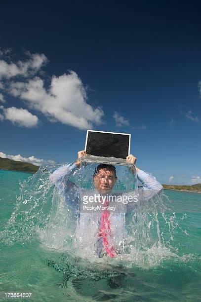 Homme d'affaires émerge de l'eau avec ordinateur portable