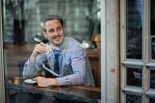Millennial businessman is laughing while enjoying a cup of coffee in a cafe before work.
