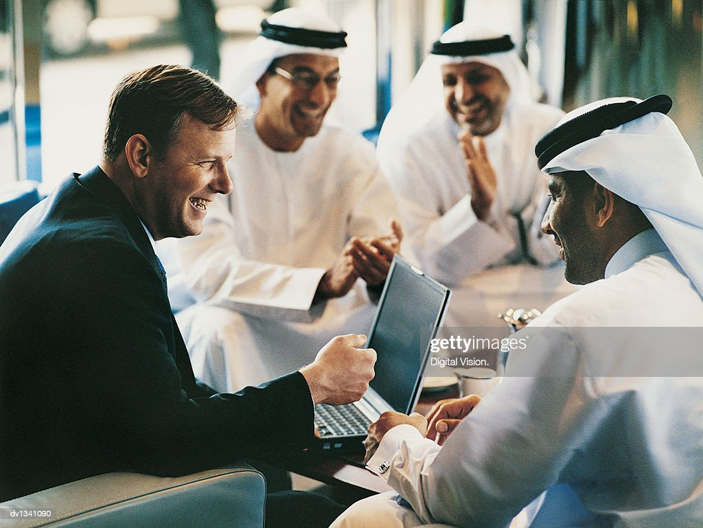 Businessman Enjoying a Discussion at a Meeting With Three Men in Traditional Middle Eastern Dress