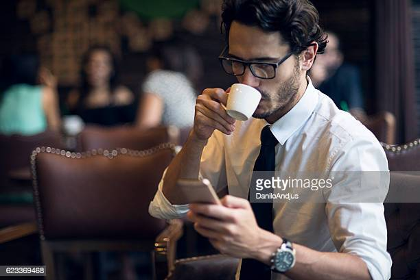 businessman enjoying his coffee and using his smartphone