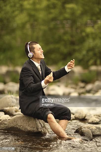 Businessman Enjoying Listening to Music at River
