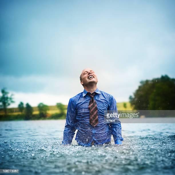 Businessman enjoying rain in a lake