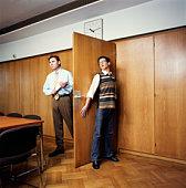 Businessman entering room, young man hiding behind door