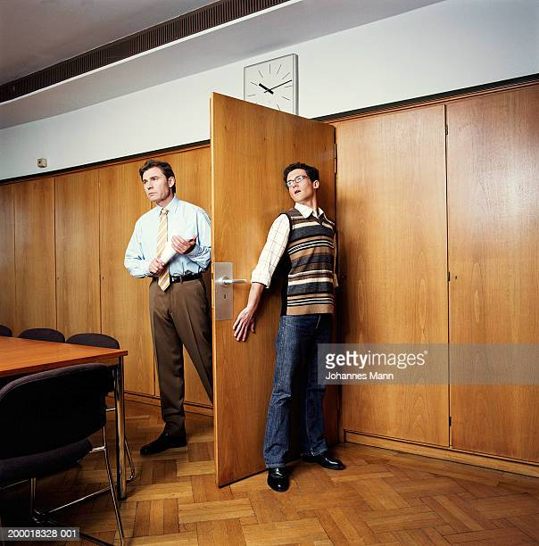 Businessman entering room, young man hiding behind door