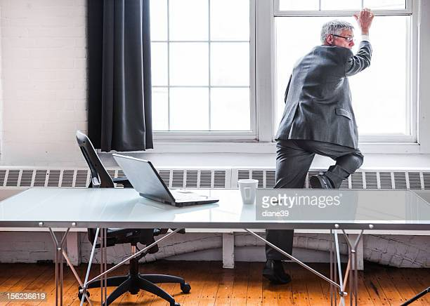 Businessman escaping or jumping out of an office window