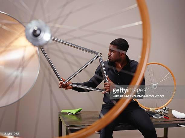 Businessman examining bicycle part