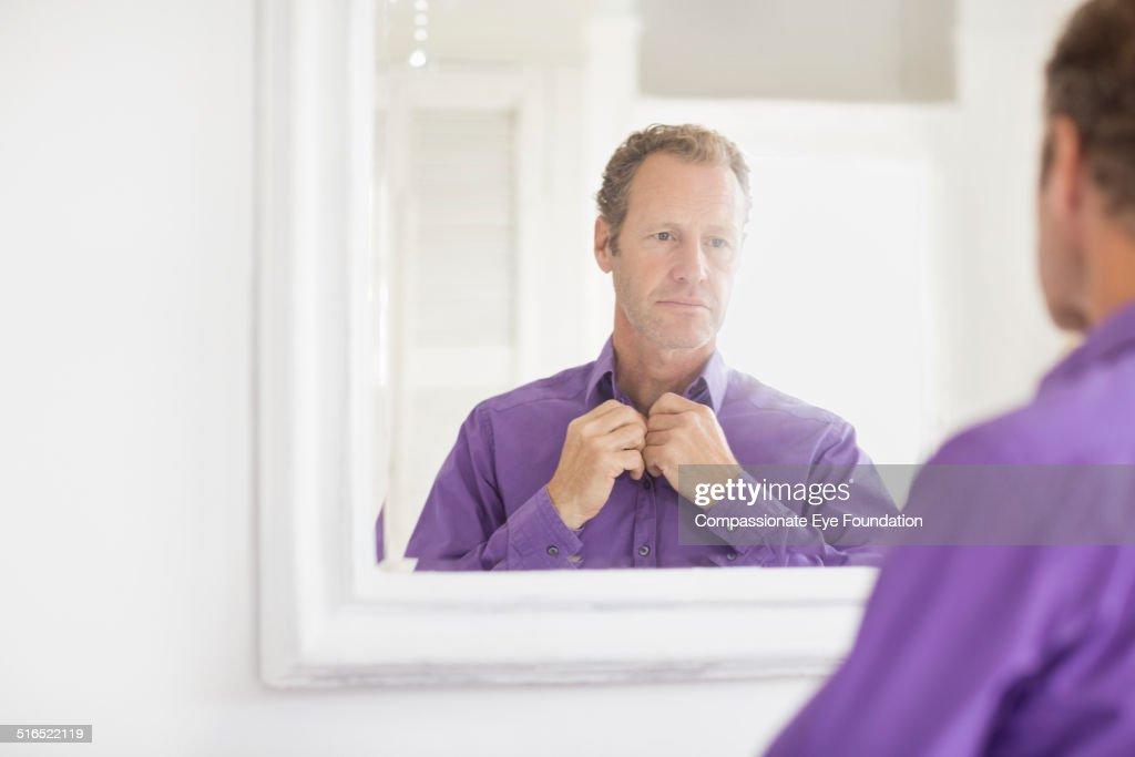 Businessman examining himself in mirror