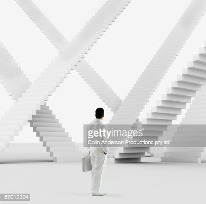 Businessman examining multiple identical staircases : Stock Photo