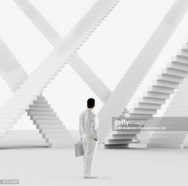 Businessman examining multiple identical staircases