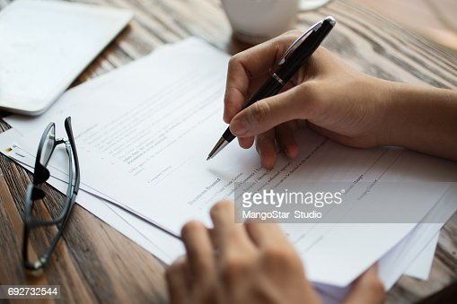 Businessman examining papers at table : Stock Photo