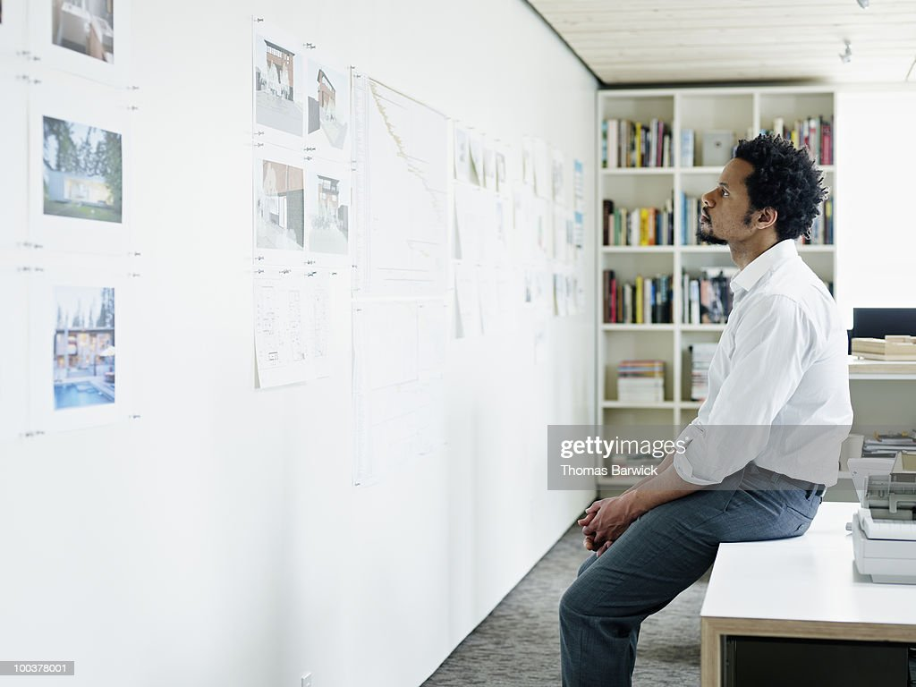 Businessman examining plans on wall of office : Stock Photo