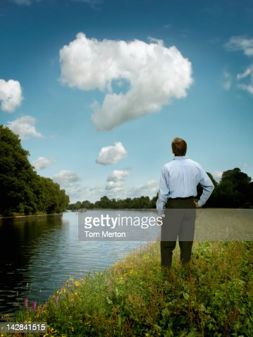 Businessman examining question mark in clouds : Stock Photo