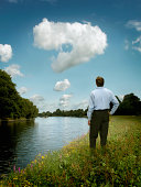 Businessman examining question mark in clouds