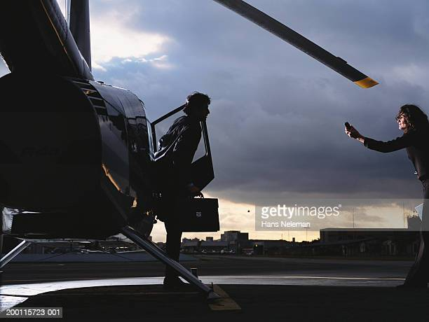 Businessman exiting helicopter, dusk