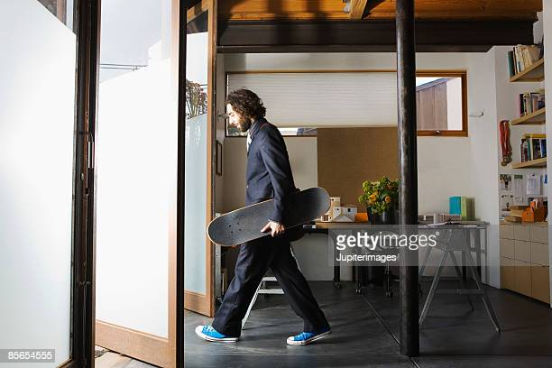 Businessman exiting office holding skateboard