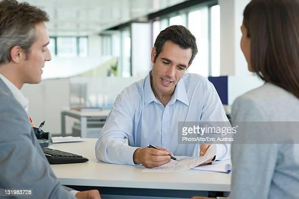 Businessman explaining document to clients