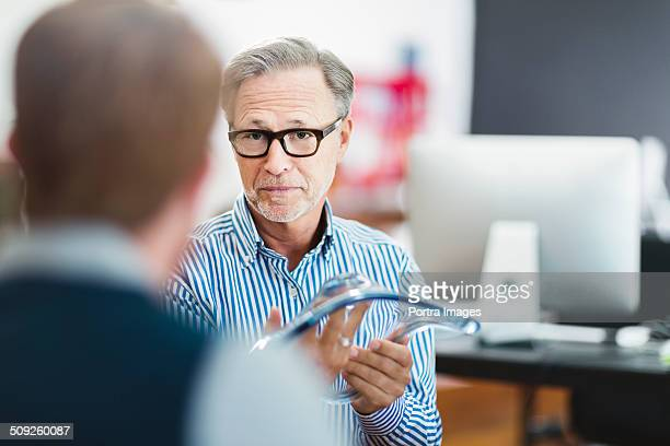 Businessman explaining glass model to colleague