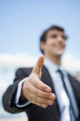 Businessman extending hand for handshake, low angle view