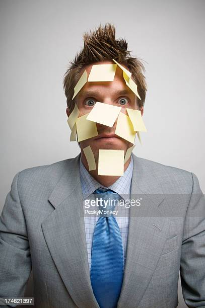 Businessman Face Covered in Yellow Sticky Notes Looking at Camera