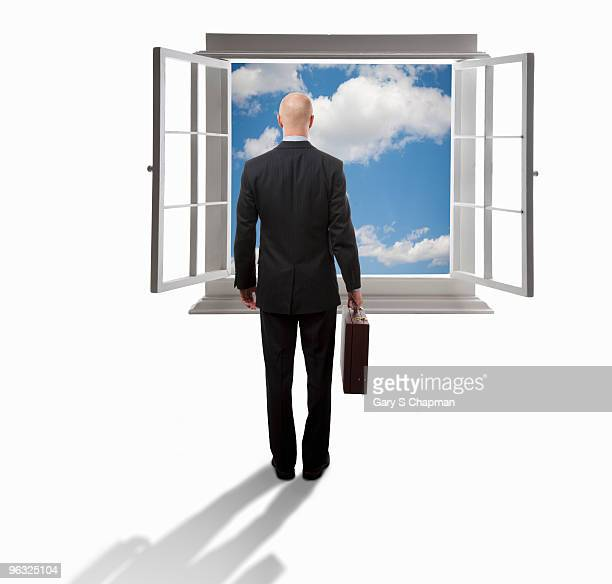 Businessman facing open window with blue sky