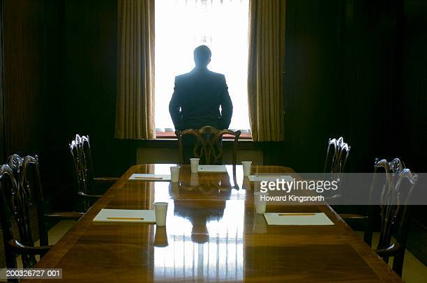 Businessman facing window in meeting room, rear view