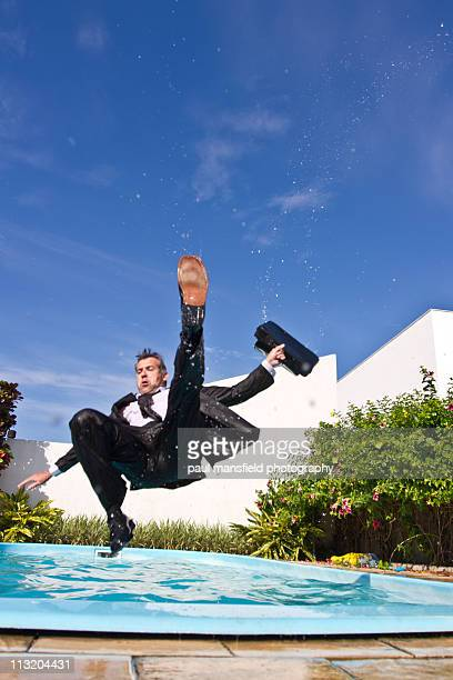 Businessman falling into swimming pool